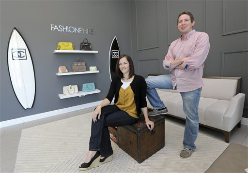 Sarah Davis and Ben Hemmnger, co-owners of Fashionphile.com, pose in the lobby of their Carlsbad, Calif. office on Thursday. The company sells rare, vintage and discontinued previous owned bags, and is facing the complicated task of dealing with new state regulations on Internet sale taxes.