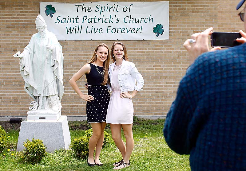 Austin Taylor of Portland photographs his daughter Rachel Taylor, 16, left, and Meghan Connolly, 15, next to the statue of Saint Patrick before the final service at St. Patrick Church. The girls were St. Patrick School classmates before it closed in 2007.