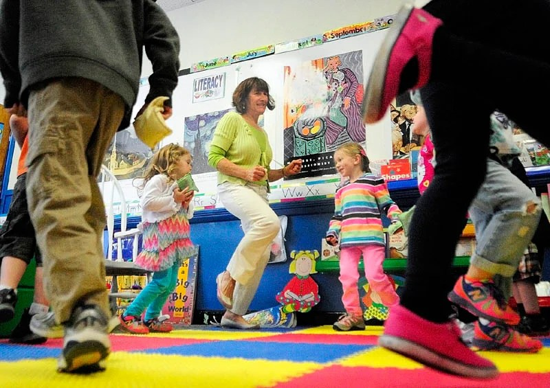 """Teacher Karen Toothaker, center, leads her students as the sing and dance along to a recording of """"The Bean Bag Alphabet Rag"""" during a pre-kindergarten class at Manchester Elementary School in this 2014 file photo."""