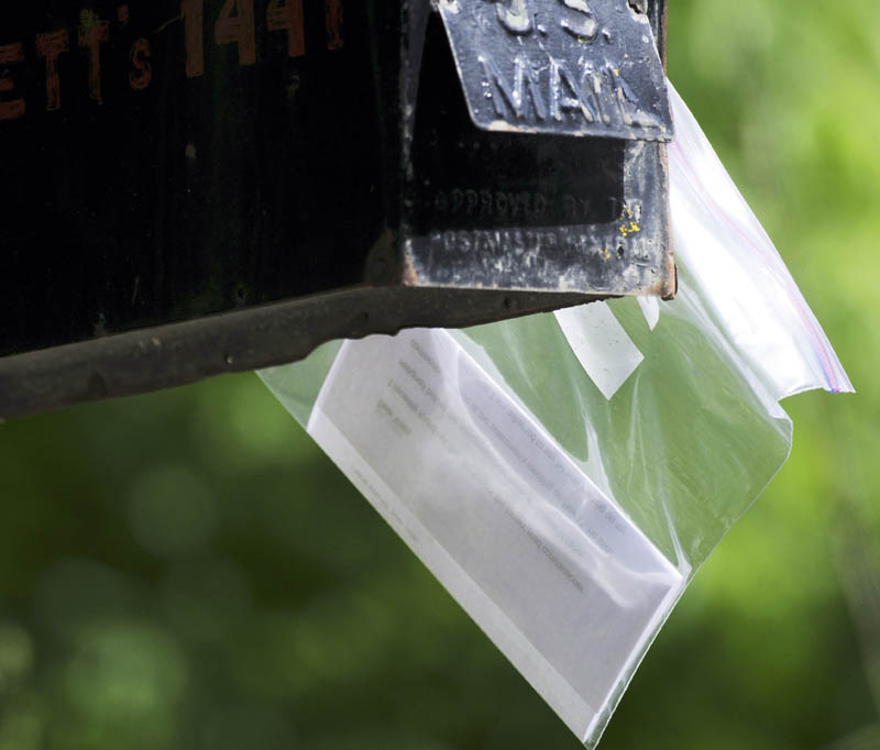 A letter enclosed in a plastic bag is attached to a Farmingdale mailbox Monday. Several people have reported receiving similar notes, that James Grant, a Board of Selectmen candidate, claims is forged with his signature.