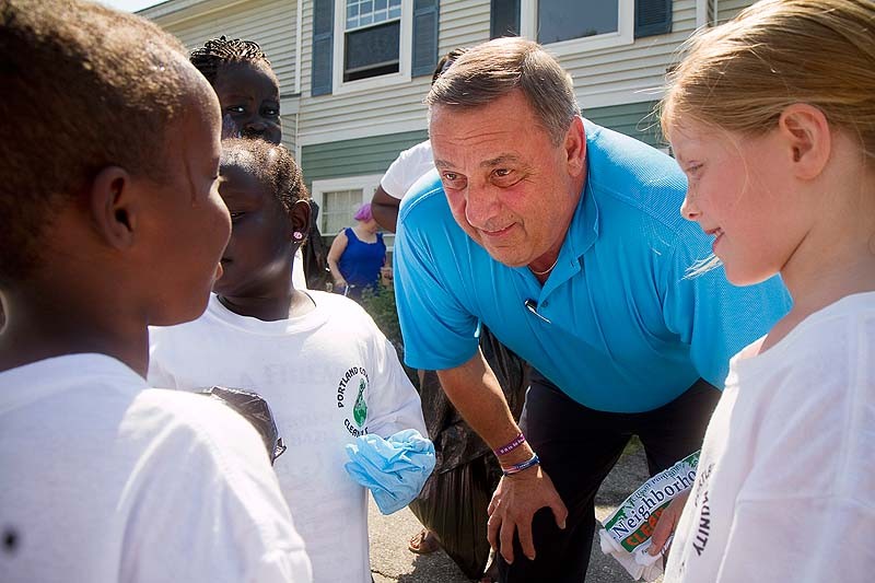 Governor Paul LePage talks with children during his visit to the Wellesley Estate in Portland during the Portland Community Cleanup Day on Saturday.