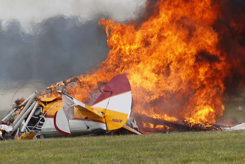 Flames erupt from a plane after it crashed at the Vectren Air Show at the airport in Dayton, Ohio, on Saturday. The crash killed the pilot and stunt walker on the plane instantly, authorities said.