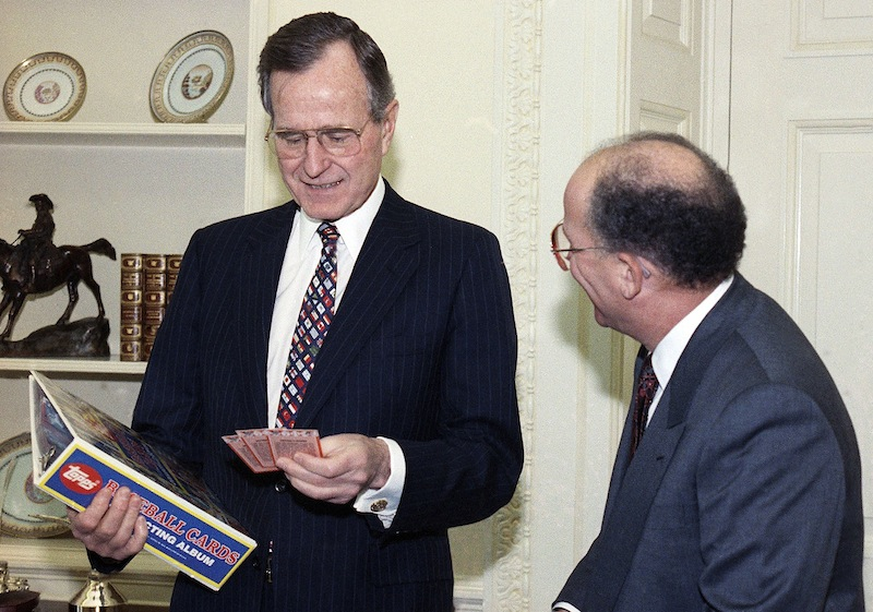 In this Feb. 5, 1990 file photo, President George H.W. Bush jokes with Arthur Shorin, President of Topps, Co., Inc., after Shorin presented him a book of baseball cards during a meeting in the Oval Office in Washington. Baseball cards depicting the former president as a Yale first baseman have fetched thousands of dollars each since they were specially-made for the White House in 1990. But Joe Orlando, president of Professional Sports Authenticator in Santa Ana, Calif., said Tuesday, July 9, 2013, that many of the Bush cards in circulation were not part of the set presented to the president.