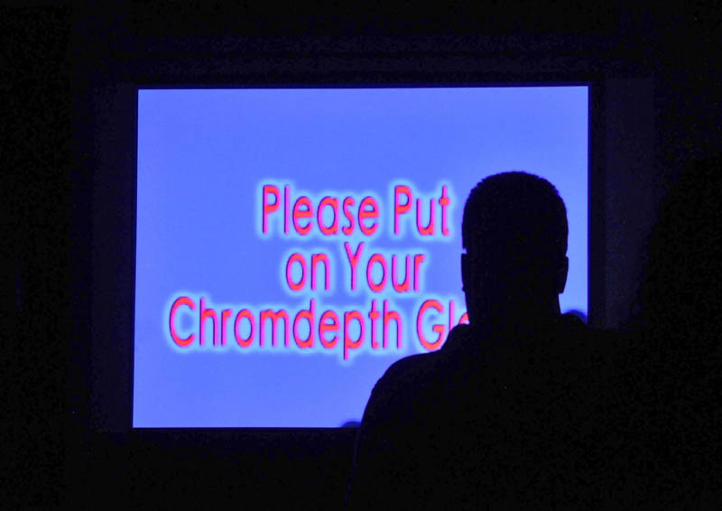 """A Maine International Film Festival-goer watches Kerry Laitala's """"Chromadepth Works"""" at the old post office in downtown Waterville on Saturday."""