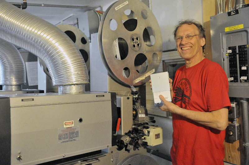 Alan Sanborn, manager at Railroad Square Cinema, holds a digital movie as he stands next to the old 35 mm projectors on Thursday.