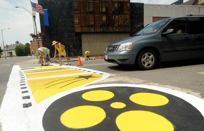 Pat Burdick, right, and her covivant, Kevin James, left, paint a new Maine International FIlm Festival themed crosswalk on Main Street in downtown Waterville on Sunday. The crosswalk was styled to go along with the annual festival, scheduled to kick off July 12.