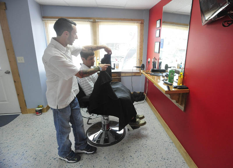 Derrik Vigue finishes up a cut on Josh Gilbert, 23, of Oakland, during a cut at Faded Lines Barber Shop at 99 Church St. in Oakland on Thursday.