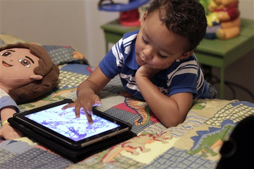 """Frankie Thevenot, 3, plays with an iPad in his bedroom at his home in Metairie, La., in this October 2011 photo. The American Academy of Pediatrics discourages any electronic """"screen time"""" for infants and toddlers under age 2, while older children should be limited to one to two hours a day."""