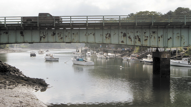 """A pickup truck drives on a bridge over Sagamore Creek in Portsmouth, N.H. on Sept. 4. According to federal records from 2012, the bridge is one of several in New Hampshire that are considered both """"structurally deficient"""" and """"fracture critical."""""""