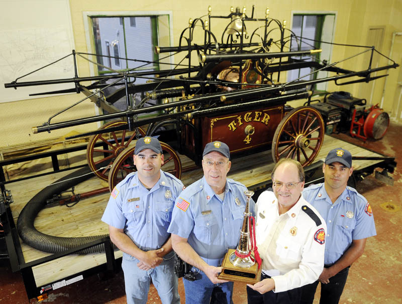 Hallowell firefighters Lt. Roy Girard, left, Capt. Richard Clark, Chief Michael Grant and Ryan Girard display a trophy Wednesday that the volunteer company received Sept. 14, for exhibiting the department's Tiger engine at the 50th annual Maine State Federation of Firefighters Convention in Ellsworth. The 1836 fire pump was recognized by the federation during the convention's parade, Grant said, after the firefighters devoted several hours prepping it.
