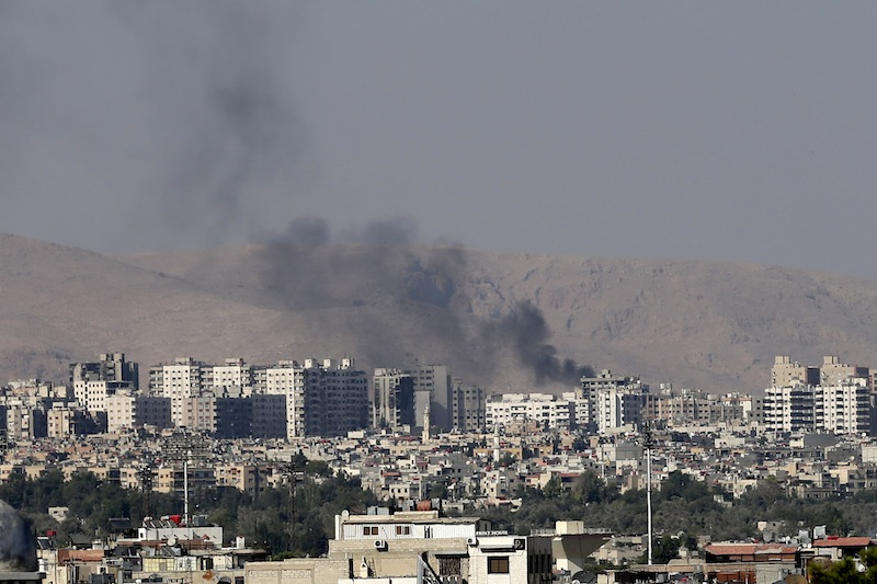 Black columns of smoke from heavy shelling in Barzeh, a suburb of Damascus, Syria, Friday, Aug. 23, 2013. U.N. inspectors reported Monday, Sept. 16, 2013 'indisputable' evidence that rockets loaded with the nerve agent sarin had been fired from an area where Syria's military has bases. (AP Photo/Hassan Ammar)