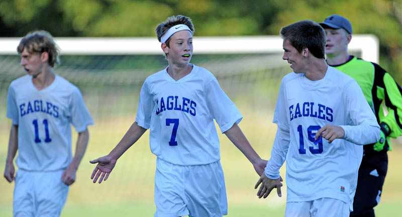 GOOD JOB GUYS: Erskine Academy's Kyle Zembroski (7) congratulates teammates Phoenix Throckmorton, left, and Mark Buzzell, right, after they beat Mt. View High School 2-1 on Tuesday at Erskine Academy in South China.