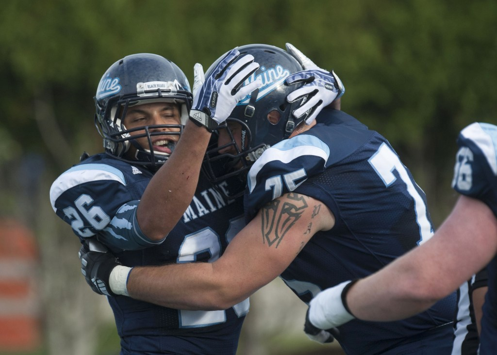 Maine running back Nigel Jones (26) and teammate Joseph Hook (75) celebrate in the first half of an NCAA college football game against Delaware in Orono, Maine, Saturday, Oct. 5, 2013.