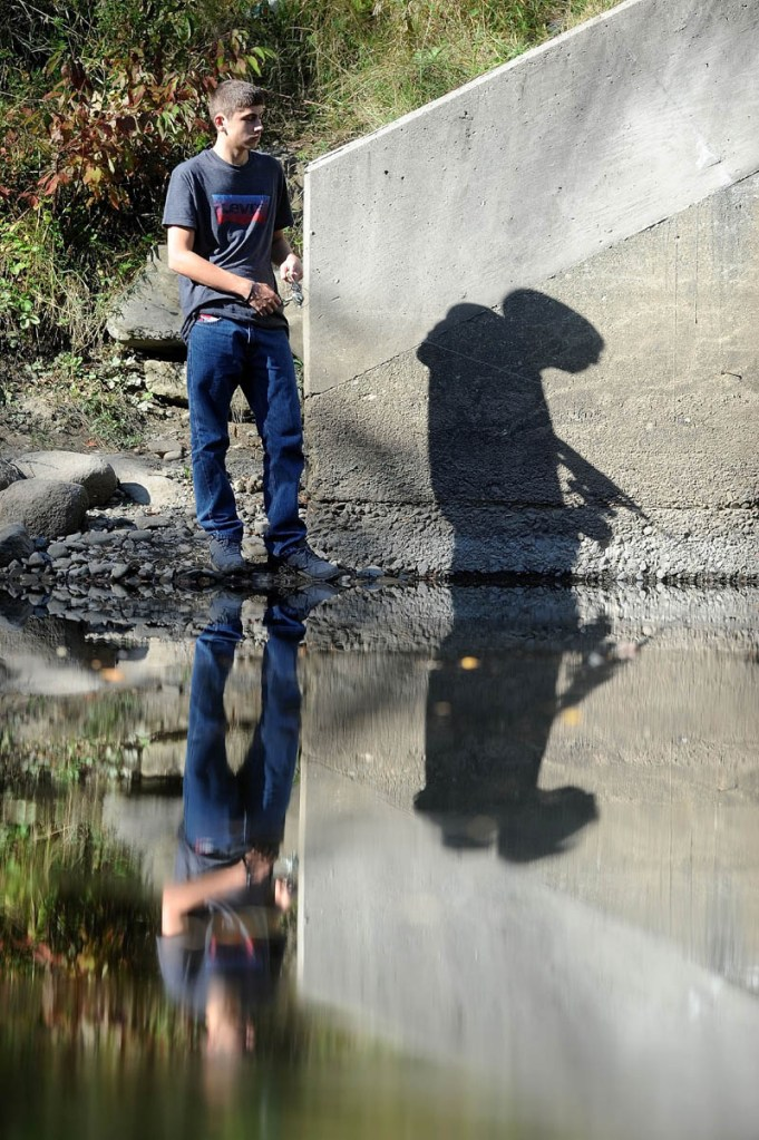 Michael Evans, 16, tries his luck fishing in the summerlike weather on Messalonskee Stream near County Road in Oakland on Sept. 27.