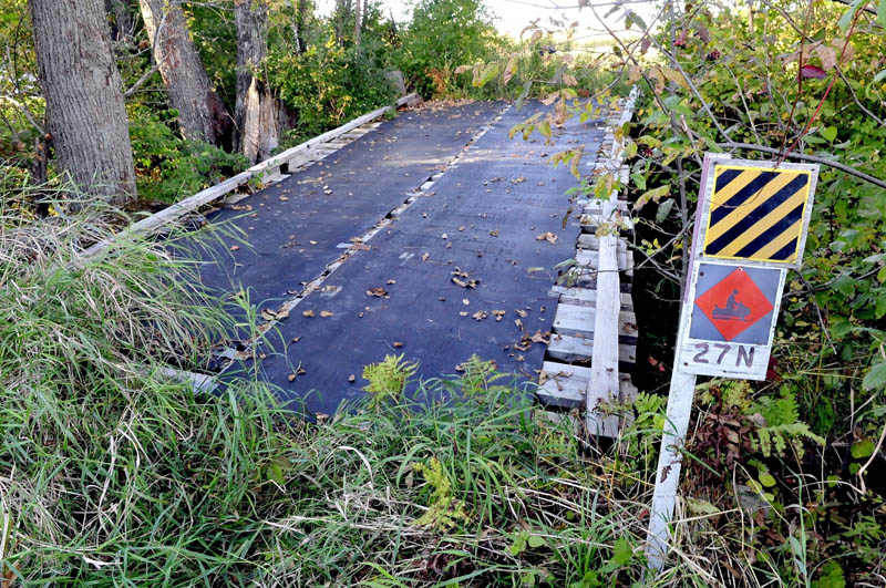 Staff photo by David Leaming MAINTENCE: The snowmobile bridge on ITS 27 in Madison is in need of repair after a tree toppled on it recently. Abnaki Sno-Riders club members are seeking more volunteers to help maintain area trails.