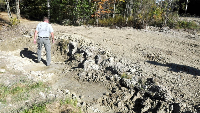 Tom Moore, former trailmaster for the Abnaki Sno-Riders club, inspects a culvert on a spur off the ITS 87 trail in Madison that a neighbor created. Moore said additional volunteer help is needed to maintain area trails, which is currently performed by a handful of members.