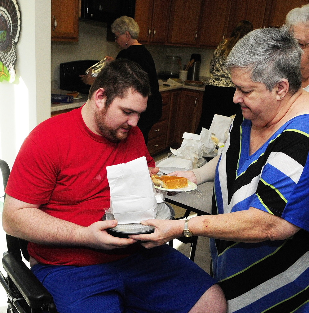 Thanksgiving Meal: Frank Jenkins, left, gets a meal from Margaret Pettnegill today at Chateau Cushnoc in Augusta. There were over 30 meals delivered there and Pettengill and other volunteer residents divided them up amongst fellow residents.