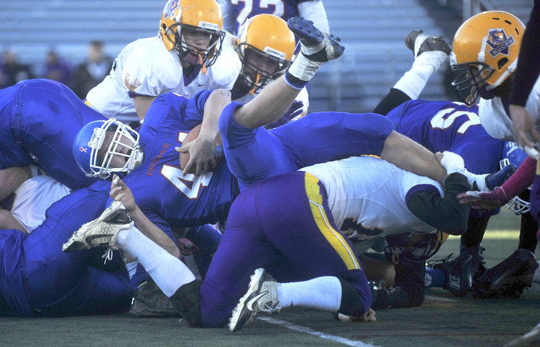 Staff photo by Michael G. Seamans CLASS D FOOTBALL:Oak Hill High School's Kyle Flaherty, 44, dives over the pile of Bucksport High School defenders for a second quarter touchdown in the Class D state championship game at Fitzpatrick Stadium in Portland on Saturday.