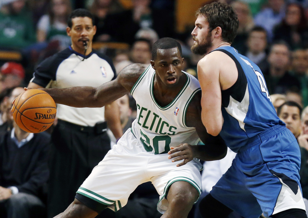 Boston Celtics' Brandon Bass (30) moves against Minnesota Timberwolves' Kevin Love (42) in the first quarter of Monday's NBA game in Boston.