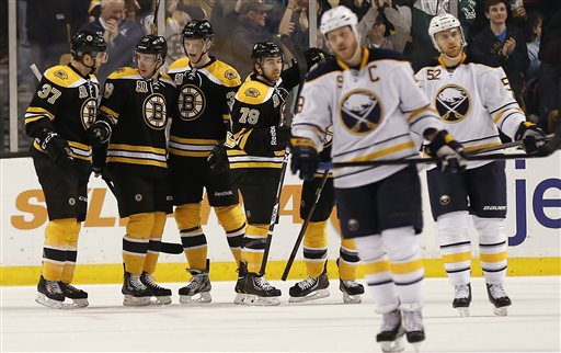 Boston Bruins' Reilly Smith, second from left, is congratulated by teammates Boston Bruins' Patrice Bergeron (37), Carl Soderberg and David Warsofsky (79) after scoring as Buffalo Sabres' Steve Ott (9) and Alexander Sulzer (52) skate away during the first period of Boston's 4-1 win in an NHL hockey game in Boston, Saturday, Dec. 21, 2013. (AP Photo/Winslow Townson)