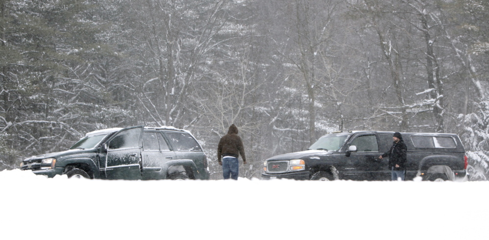 Gregory Rec/Staff Photographer A motorist in a truck stops to help a driver who got stuck in a snowbank in the southbound lane of the Maine Turnpike in Arundel on Friday.