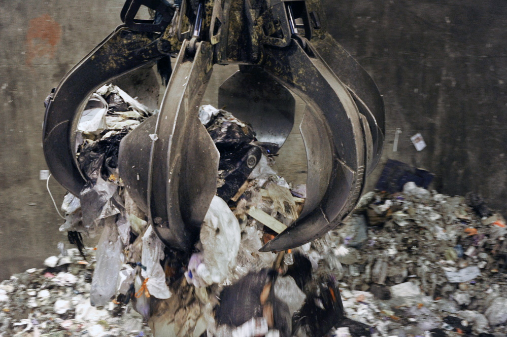 A bucket loader moves trash at ecomaine's processing facility in Portland.