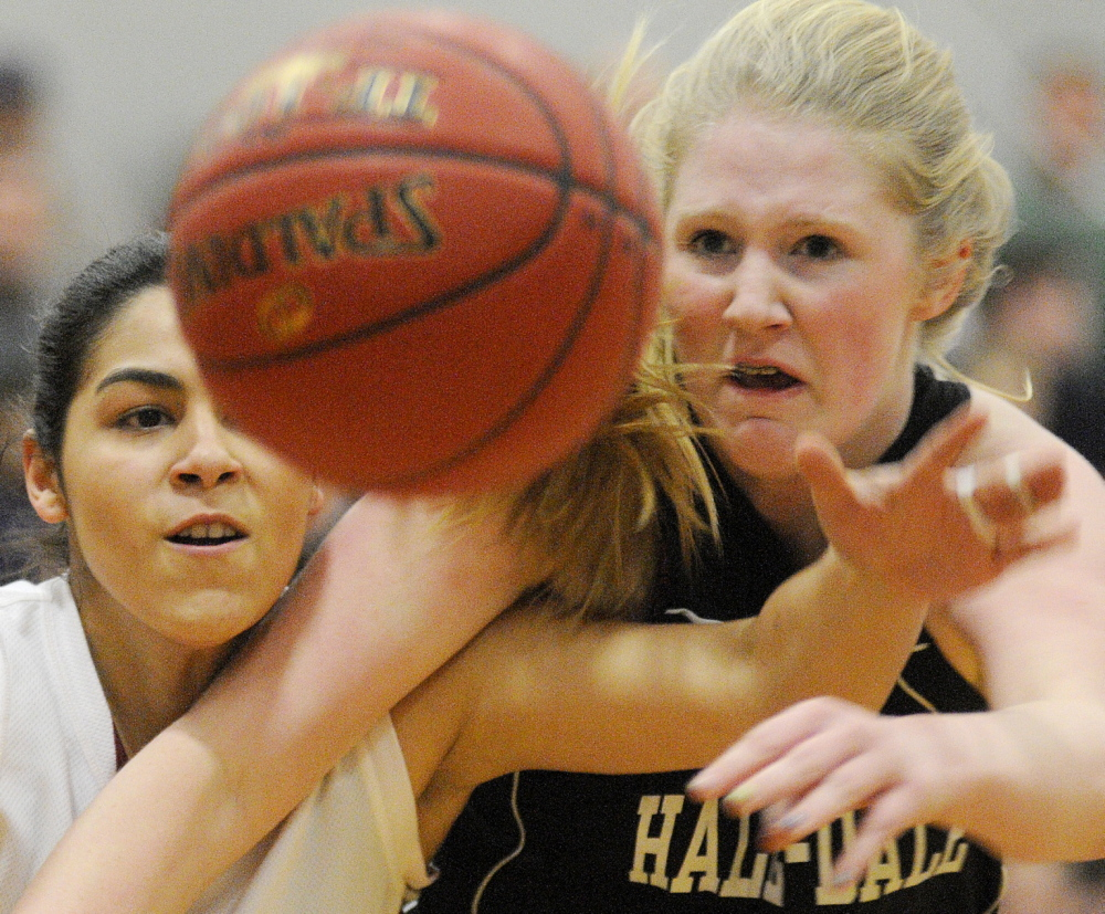 Staff photo by Andy Molloy OVER THE TOP: Kents Hill School's Liz Torres, left, Hall-Dale High School's Brooke Berberich go for a ball during their Western C prelim match Tuesday in Readfield.