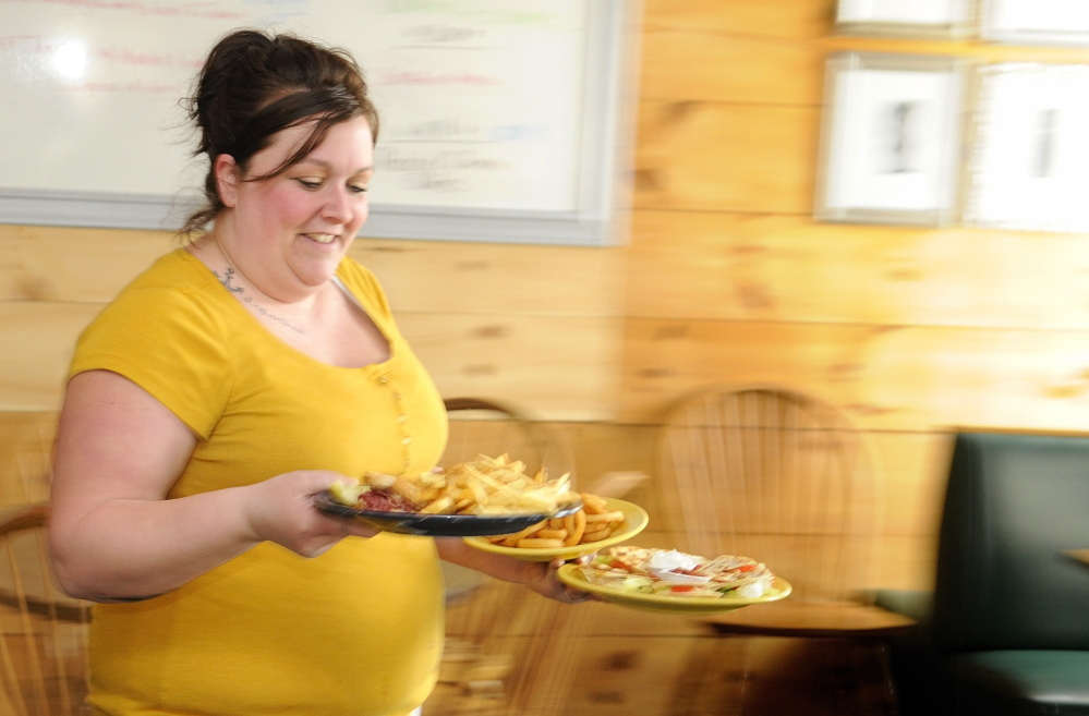 BUSINESS GOOD: Waitress Jessica Grant carries lunch out to a table for customers on Friday at Lisa's Restaurant and Catering on Bangor Street in Augusta.