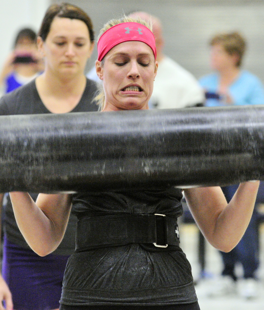 Up Lifting: Annie Philbrick grimaces as she sets down the log after making a lift in the women's novice division of max log clean during the Central Maine Strongman 7 competition on Saturday at Augusta Armory. Increasingly heavier weights are added to the metal log each round until only one last competitor can the lift it.