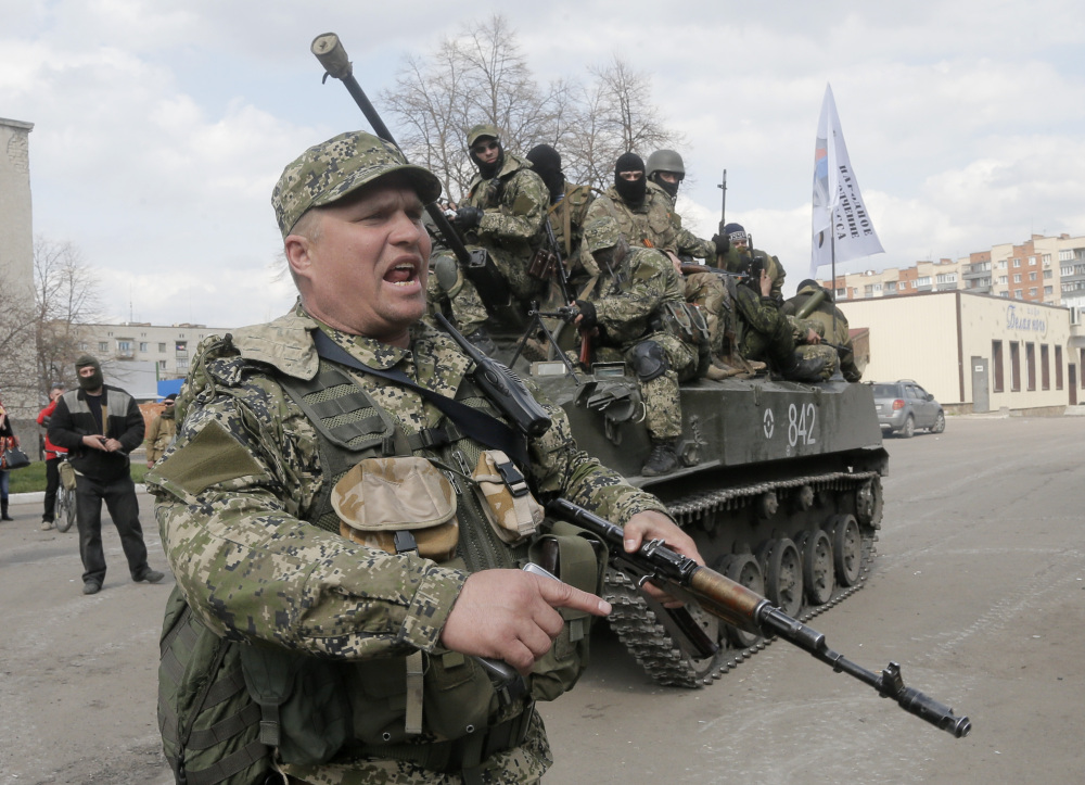 A pro-Russian gunman clears the way for a combat vehicle with gunmen on top in Slovyansk, Ukraine, Wednesday.