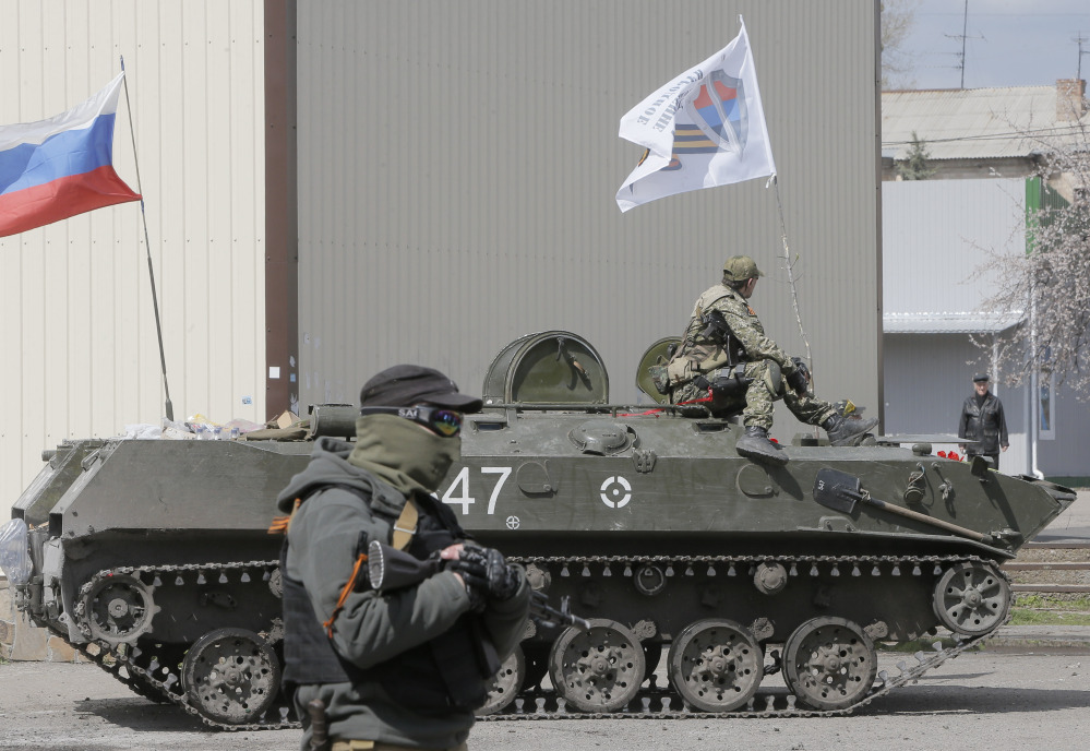 A masked gunman guards combat vehicles with Russian and Donetsk insurgency army flags and gunmen on top, parked in downtown of Slovyansk on Wednesday. One of the on those vehicles wore a St. George ribbon attached to his uniform, which has become a symbol of the pro-Russian insurgency in eastern Ukraine.