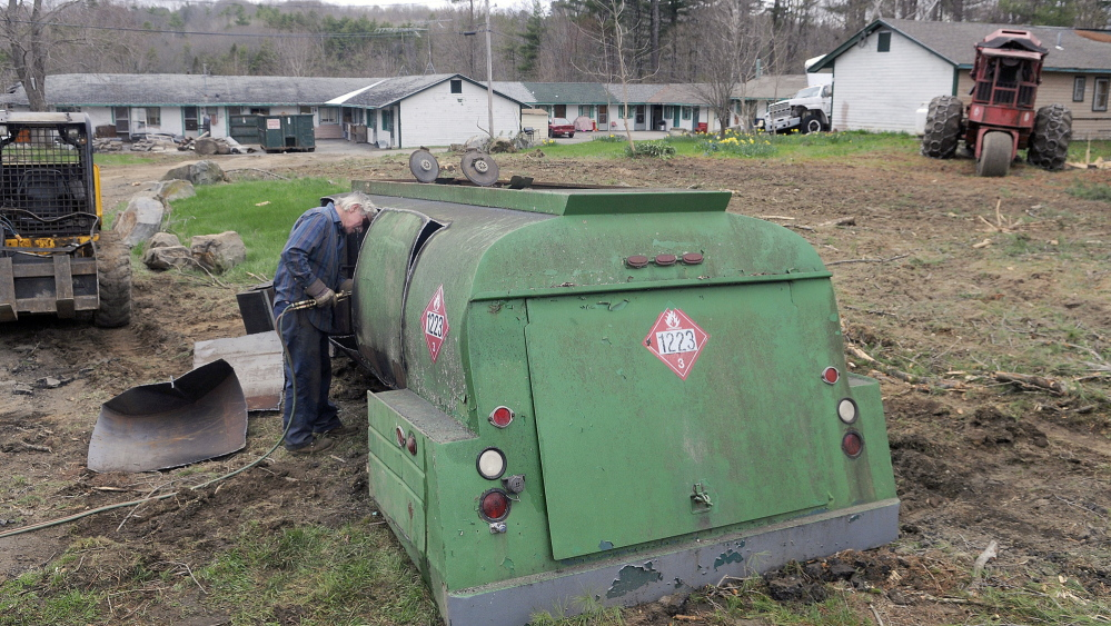 CLEAN-UP: Neal Maine cuts apart a fuel truck Tuesday at the Country Village Motel and Apartments in Augusta, part of the effort to clean up debris at the complex so it can comply with city codes.