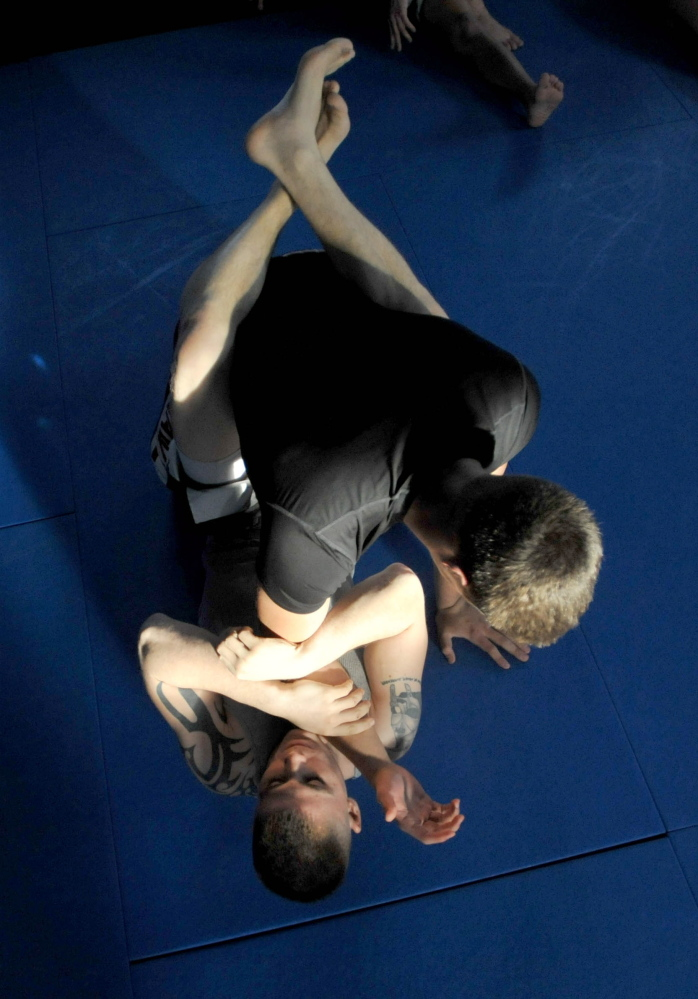 SPAR: Phillip Exner, wearing gray, spars with Chad Martin during a mixed martial arts training session at Littlefield's Gym in Oakland on Thursday.