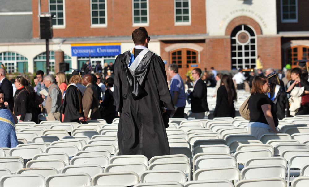 A Quinnipiac University graduate looks for relatives Sunday after university officials decided to move the graduation ceremony from the main campus because of bomb threats.