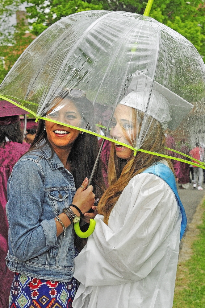 SHIELDED: Carmen Adams, left, holds an umbrella over herself and graduate Sarah Grenier as a shower blows through before the graduation ceremony Saturday at Kents Hill School in Readfield.