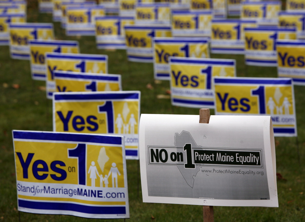 """Posters urging Mainers to vote to repeal the state's same-sex marriage law are displayed in Portland in 2009, along with a """"No on 1"""" campaign poster. Maine's ethics panel found that the National Organization for Marriage concealed its operations and donors during the campaign."""