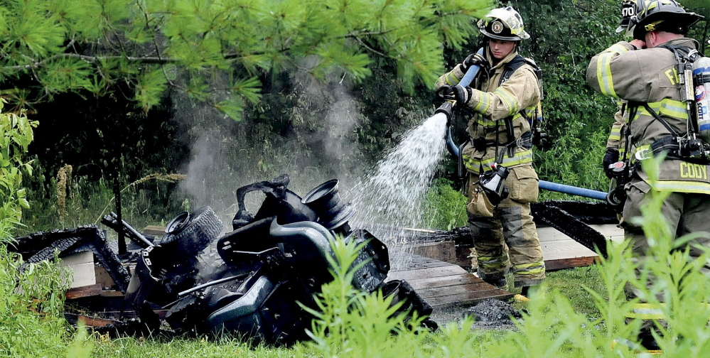 Fairfield firefighters spray water onto the smoldering remains of a lawnmower that burned Sunday after it was used and placed in a utility shed in Benton. The shed also caught fire.