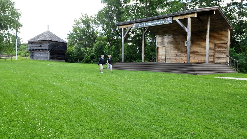 Nancy Gaunce, left, and Millie Meers walk in Fort Halifax Park in Winslow between the historic fort building and the Mary Simcock pavilion. Plans are underway to restore the fort to its original setting, install walkways and relocate the parking area.