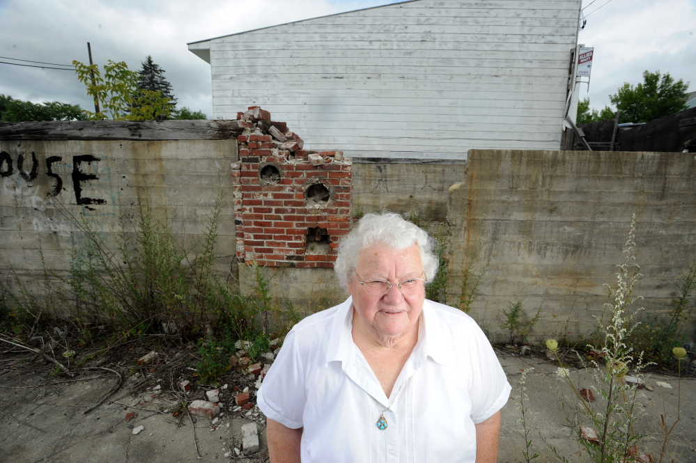Alice Emery stands in the foundations of two burned out buildings she has bought and donated to the town of Norridgewock for development on Friday.