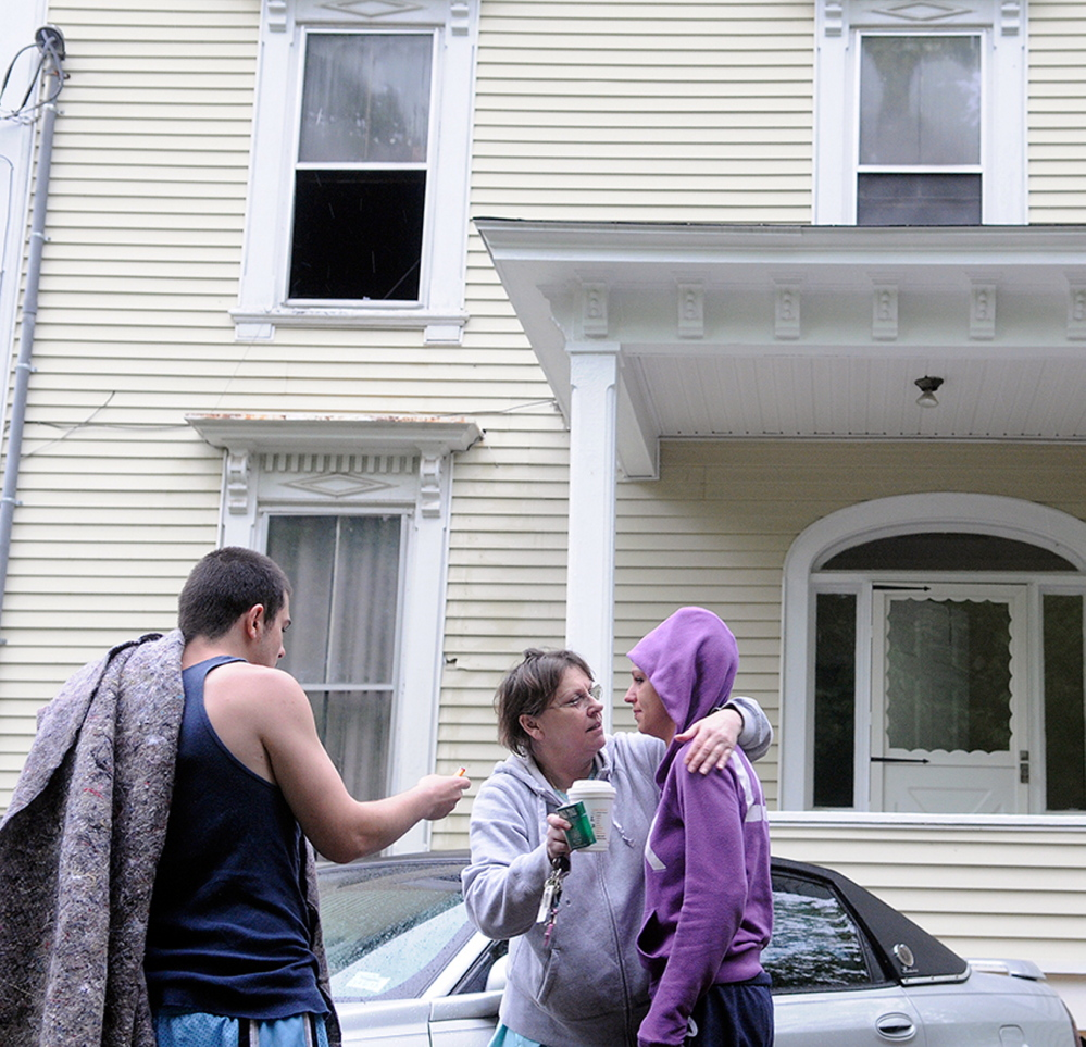 Jackie Nelson, center, hugs her granddaughter, Sabrina Moulton, the building's owner, on May 27 after an early morning fire forced them and tenant Anthony Luczkowski, left, to flee an apartment building at 11 Cedar Court in Augusta. Tenant David Malia on Tuesday was found not criminally responsible for setting the fire.