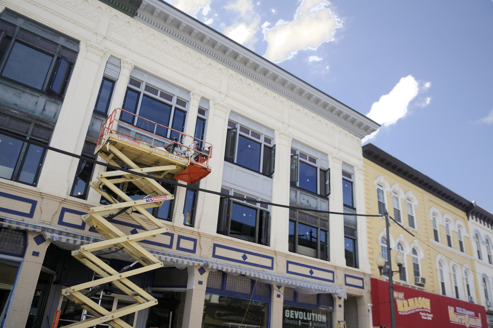 Workers renovate the exterior of 190 Water St. in Augusta on Friday, where high-end apartments are being created on the second and third floors.