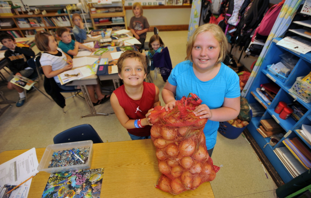 Albert S. Hall fifth-graders Jacob Luff, 11, left, and Eleanor King, 10, stand with a sack of donated onions at the school in Waterville on Wednesday.