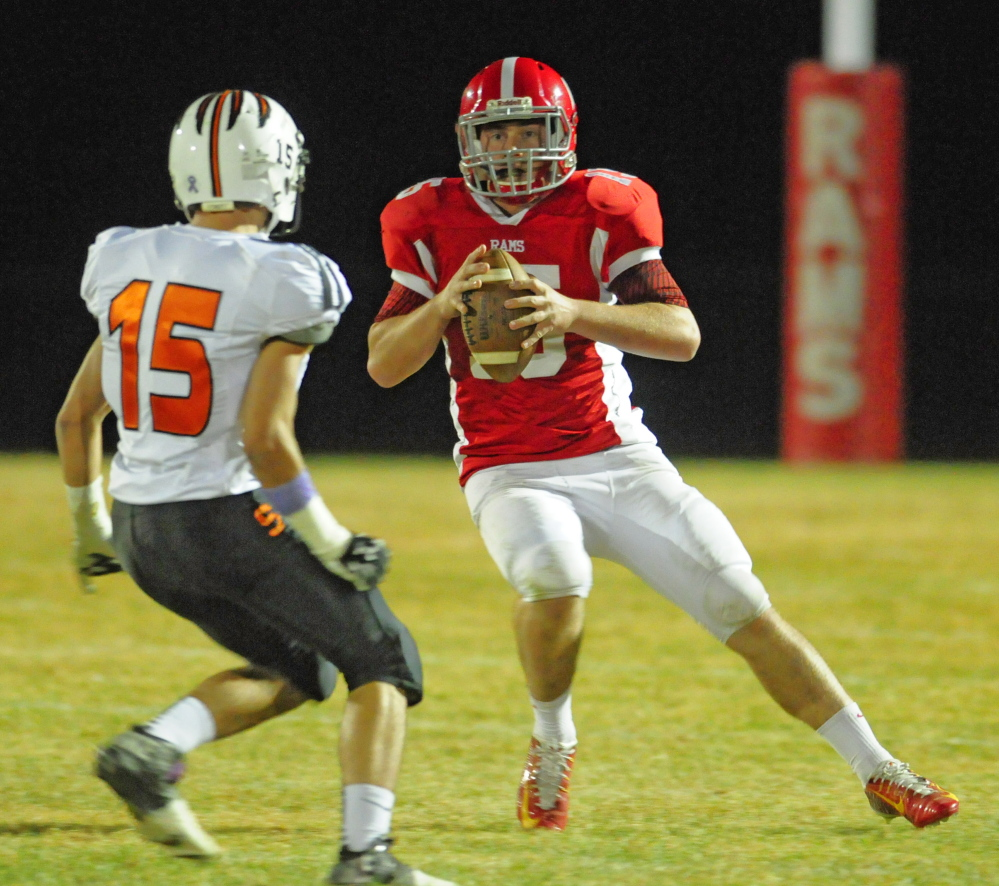 Staff file photo by Joe Phelan   Skowhegan Kam Doucette, left, chases Cony quarterback Mitchell Caron during a Pine Tree Conference Class B game Friday night. The Rams scored an important victory to keep pace with Brunswick and Lawrence.