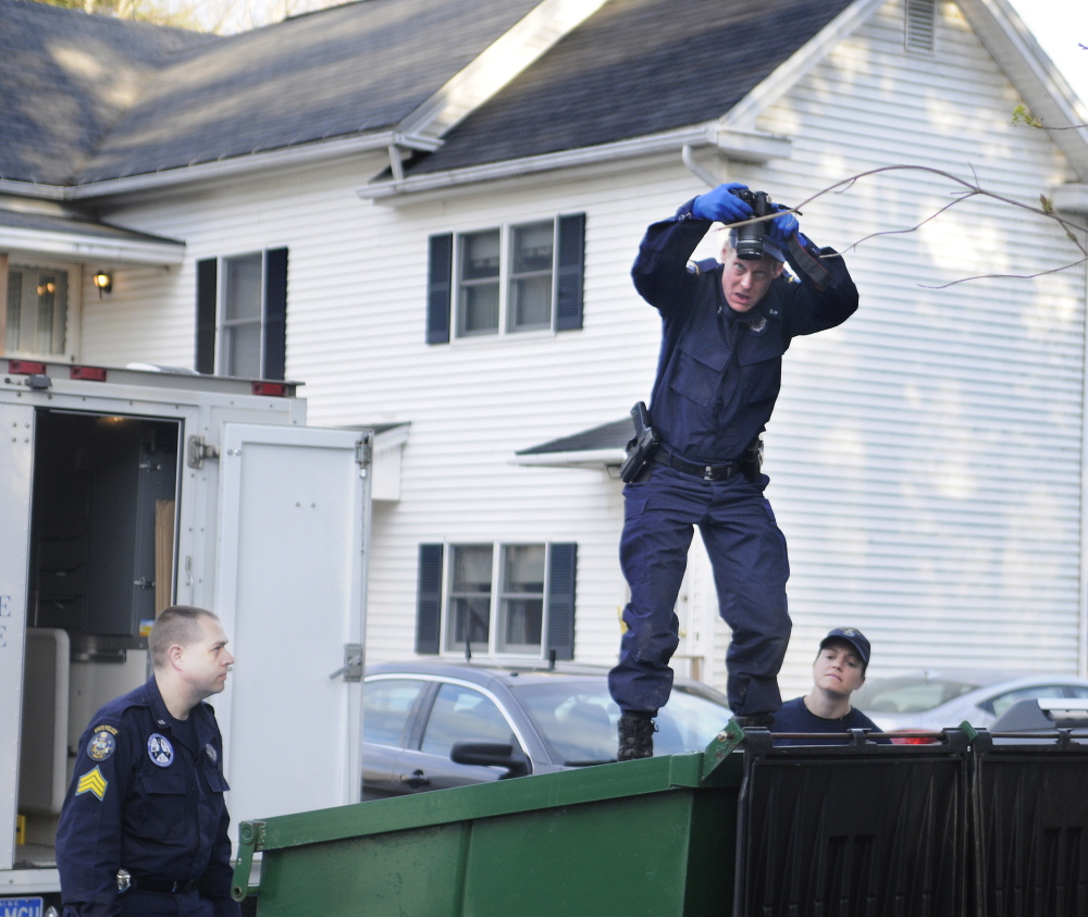 State Police Detective Terry James, center, photographs the interior of a Dumpster May 5, 2014, outside the apartment that Leroy Smith Jr. shared with his son in South Gardiner. Detective Sgt. Jason Richards, left, and Trooper Breanne Petrini searched the Dumpster in the evening after the elder Smith's body was recovered in Richmond.