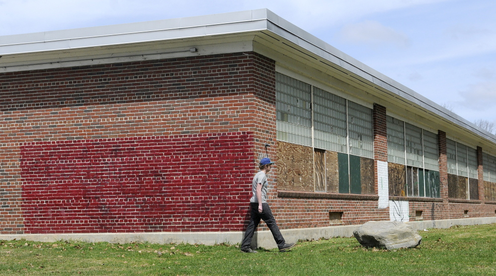 Tyler Lessard, 15, walks around the former Hodgkins Middle School in Augusta to the nature trails behind it on Tuesday. The Augusta Housing Authority and a local developer have proposed to redevelop the abandoned building into elderly housing.