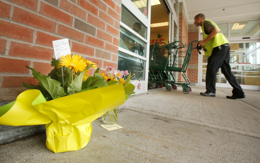 People placed flowers outside of the entrance to Shaw's supermarket in Saco on Thursday morning. Wendy Boudreau, 59, died after being stabbed  inside the store on Wednesday and police have charged Connor MacCalister, 31, with her murder. Gregory Rec/Staff Photographer