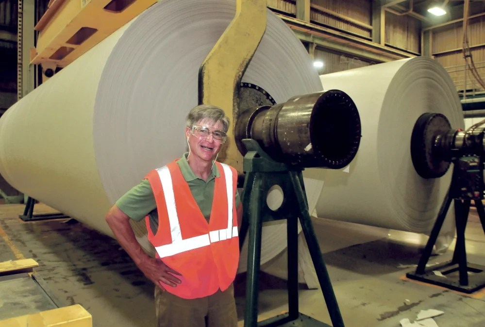 UPM Madison President and CEO Russ Drechsel beside two finished rolls of paper in Madison.
