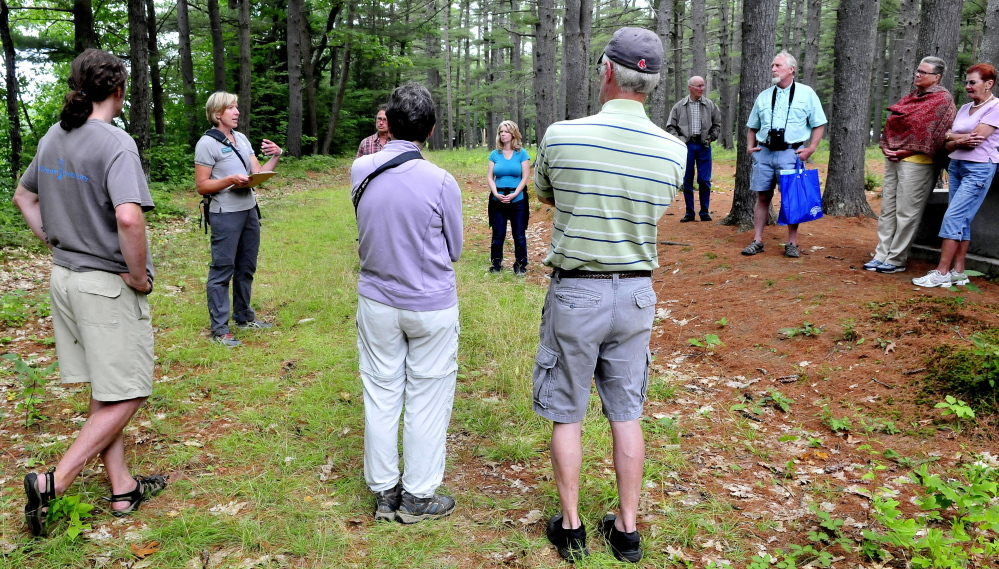 Maine Master Naturalist Kate Drummond, second from left, leads a group on an informational hike along a trail in the Pines area in Madison on Sunday. The event was part of the Madison-Anson Days celebration.