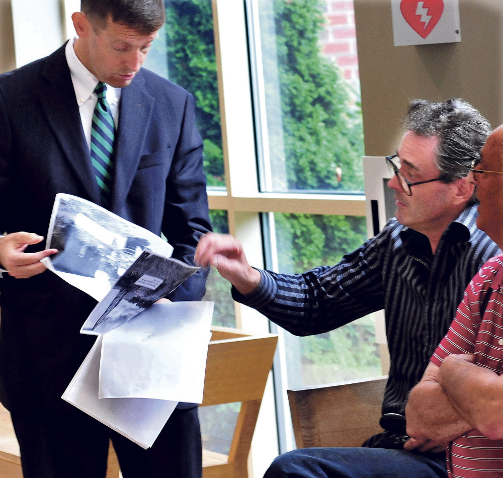 Robert Dale, right, points to images of his Fairfield business clean-up efforts to attorney Walter McKee prior to a hearing in Skowhegan District Court on Monday.
