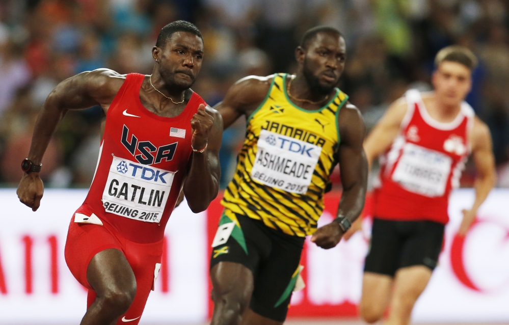 Justin Gatlin, left, races in a round one heat alongside Nickel Ashmeade of the men's 200m at the World Athletics Championships on Tuesday at the Bird's Nest stadium in Beijing.